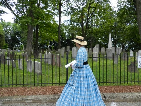 Woman in historical clothing walks through cemetery