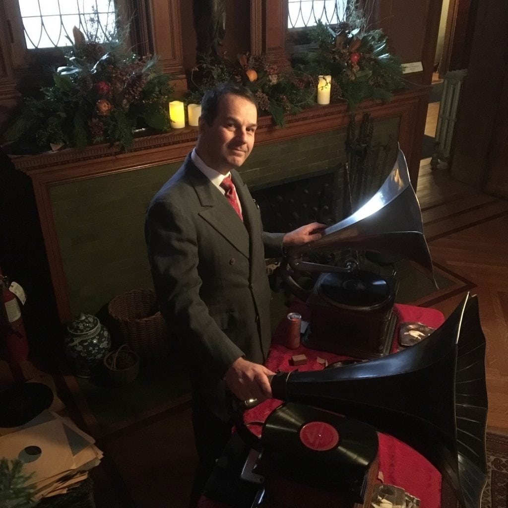 Man in a suit playing records from old record players