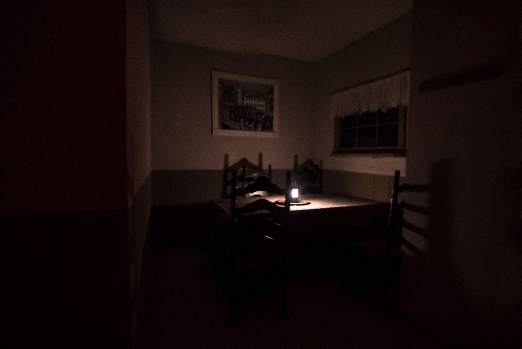 dark room with table and single lantern