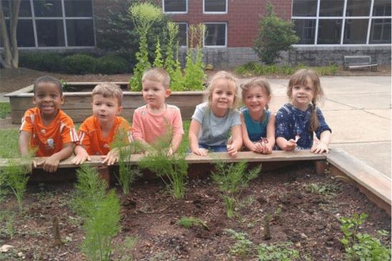 six children sitting outside