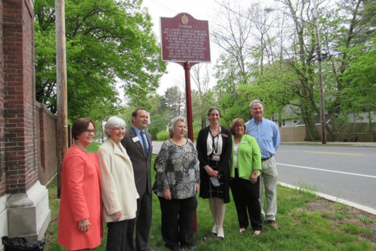 seven adults standing for picture in front of morris county sign