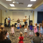 band playing concert for young children