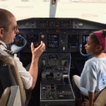 young girl in cockpit of airplane with pilot