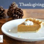pumpkin pie on a white plate with pine cones