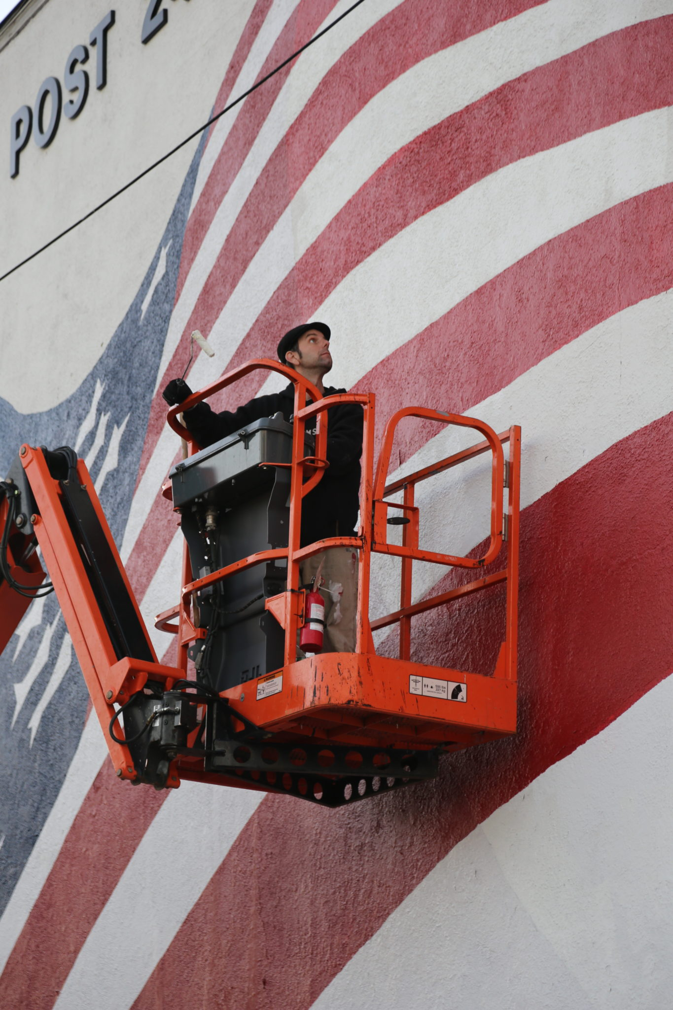Exterior image of man on a crane painting a mural for Boonton Arts mural project