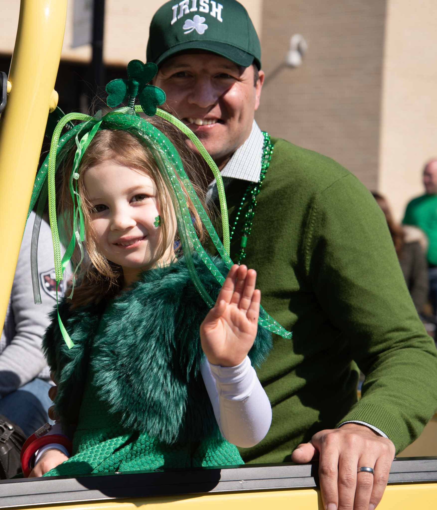 Girl and her father at the St. Patricks Day parade waving